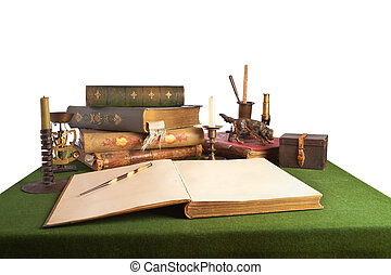 Desk with an open book and old stationery. Isolated on white...