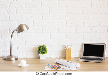 Creative designer desktop with blank laptop screen, plant, coffee cup, sketches, colorful pencils, lamp and other items on white brick wall background. Mock up