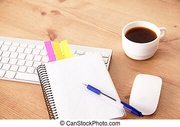 Desk with laptop, eye glasses, earphone, pen and a cup of coffee
