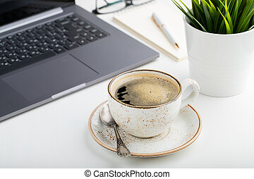 Desk with laptop, eye glasses, notepad, pen and a cup of coffee on a white table. Light background