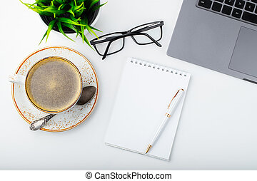 Desk with laptop, eye glasses, notepad, pen and a cup of coffee on a white table. Top view. Flat lay. Light background