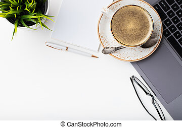 Desk with laptop, eye glasses, notepad, pen and a cup of coffee on a white table. Top view with copy space. Flat lay. Light background