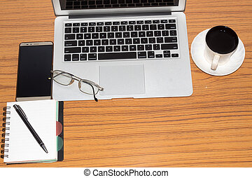 Desk with open notebook, mobile phone, eye glasses, pen and a cup of coffee. Top view with copy space. Business still life concept with office stuff on table. Education, working or planning concept