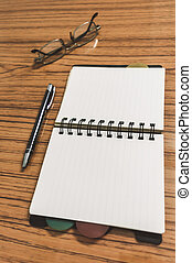 Desk with open notebook with blank pages, eye glasses and a pen. Business still life concept with office stuff on table. Education, working and planning concept. Selective focus with shallow DOF.