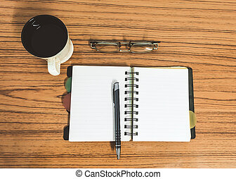 Desk with open notebook with blank pages, eye glasses, pen and a cup of coffee. Top view with copy space. Business still life concept with office stuff on table. Education, working or planning concept