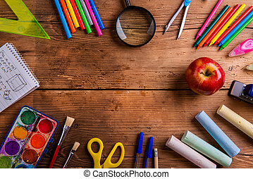 Desk with school supplies against wooden background