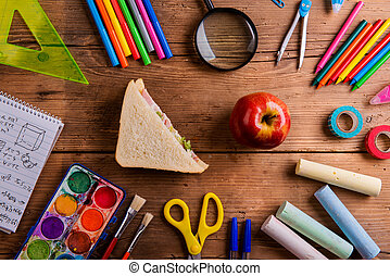 Desk with school supplies, sandwich and apple, wooden background