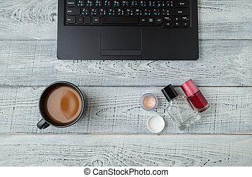 Desk. woman's workplace. laptop, coffee Cup perfume and cosmetics. the view from the top. flat lay
