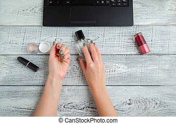 Desk. woman's workplace. women's hands, laptop, perfume and cosmetics. the view from the top. flat lay