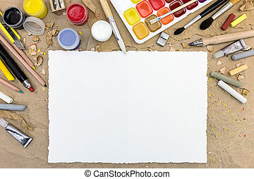 desktop with blank paper sheet and various drawing tools