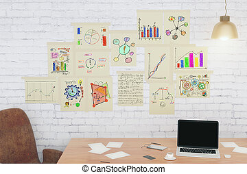 Desktop with business charts on paper on the wall, concept