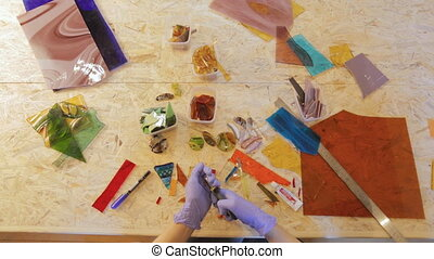desktop wizard woman working with glass, it is preparing for an offensive holidays, cuts and adds new details of their future gifts to their customers bijouterie and decorations.