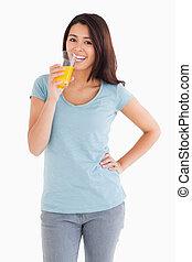 deslumbrante, mulher, bebendo, um, vidro suco laranja