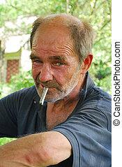Despair - Old man drunkard sitting near the fence, smoking a...