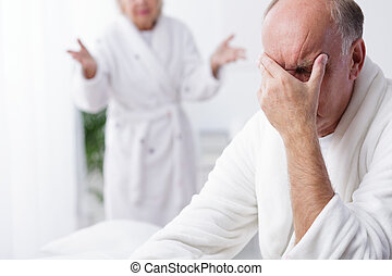 Despair senior man sitting on the bed