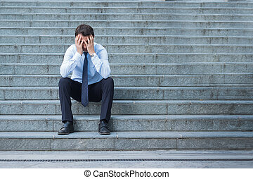 Desperate alone businessman after big fail sitting on the stairs