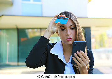 Desperate business woman looking on mobile phone her credit card statement stressed. Credit card cloned concept.