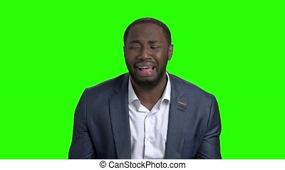 Desperate businessman crying on green screen.