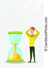 Desperate businessman looking at hourglass.