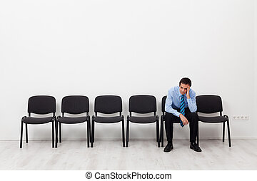 Desperate businessman or employee sitting alone prompting...