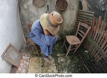 desperate farmer - pensative poor peasant sititng on a chair...