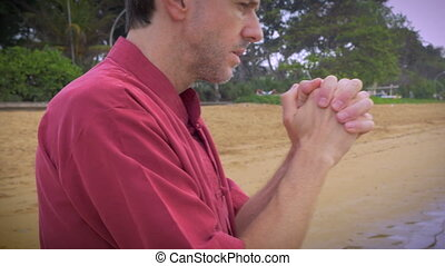 Desperate middle aged man preys on the beach for forgiveness hand held