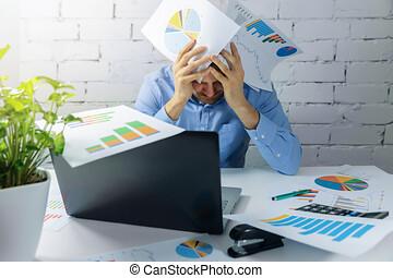 desperate overworked businessman doing paperwork in office