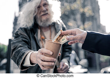 Grey-haired homeless man carrying cardboard cup and begging