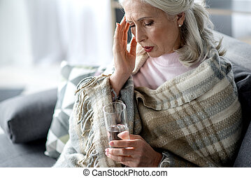 Desperate senior lady feels terrible pain in head