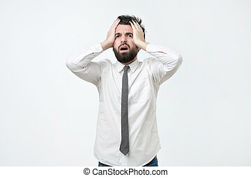 Desperate, stressed young european man looking at camera in terror and shock, holding head