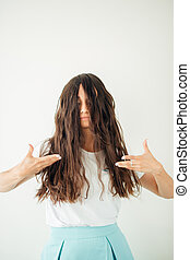 Desperate woman showing she needs haircut