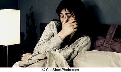 Desperate young woman crying in bed