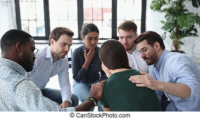 Impressionable mixed race friendly people listening complaints of unhappy depressed woman at psychological counseling meeting. Desperate young lady sharing problems with compassionate diverse friends.