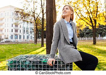despreocupado, mujer joven, sentado, en, un, banca de parque, y, reír., agradable, niña, en un buen humor, en, un, día de otoño, el gozar, el, bueno, weather.