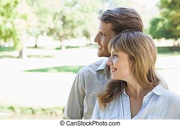 despreocupado, pareja, posición, en el parque, y, sonriente