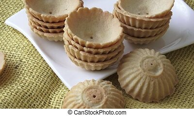 Dessert in the form of a basket. Sweet pastry on a background of yellow jute.
