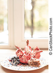 Dessert plate with pomegranate in front of window