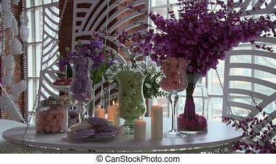 Dessert table decorated with flowers and candles