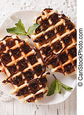 Dessert waffles with chocolate topping on a plate close-up. ...