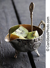 Dessert with Kiwi fruit on silver bowl and spoon. Food background.