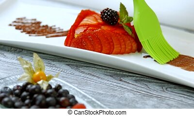 Brush smears brown substance. - Dessert with strawberry...