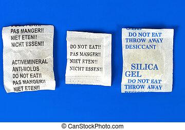 Dessicant, silica gel - Macro of silica gel bags on blue...