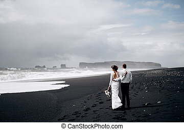 Destination Iceland wedding. A wedding couple is walking along the black beach of Vic. Sandy beach with black sand on the shores of the Atlantic Ocean. Huge foamy waves. The groom hugs the bride.