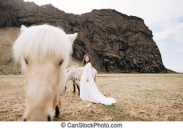 Destination Iceland wedding photo session with Icelandic horses. The bride walks across the field, near a grazing light horse.