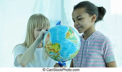 Two schoolgirls spinning the globe and choosing playfully the destination