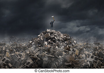 Destroy and demolish concept as a businessman standing on a mountain of building ruins holding a sledge hammer as a business or life metaphor for tearing down old industry to make room for a modern infrastructure.