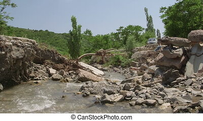 Destroyed concrete bridge over a mountain river by a flood...