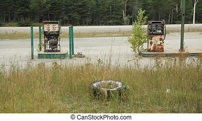 Destroyed gas pump. Car passes. - Abandoned gas pumps with...