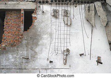 Destroyed white wall with fragments of red brick and concrete stones hanging on the reinforcement. Background