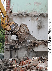 Destroying of an old house, by a machine.
